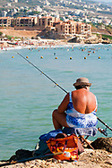 A woman fishes at a popular beach in the Mediterranean city of Byblos, located a few miles north of Beirut.