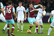 Andy Carroll of West Ham United ©  holds off  Stephen Kingsley of Swansea city. Premier league match, Swansea city v West Ham United at the Liberty Stadium in Swansea, South Wales on Boxing Day, Monday 26th December 2016.<br /> pic by  Andrew Orchard, Andrew Orchard sports photography.