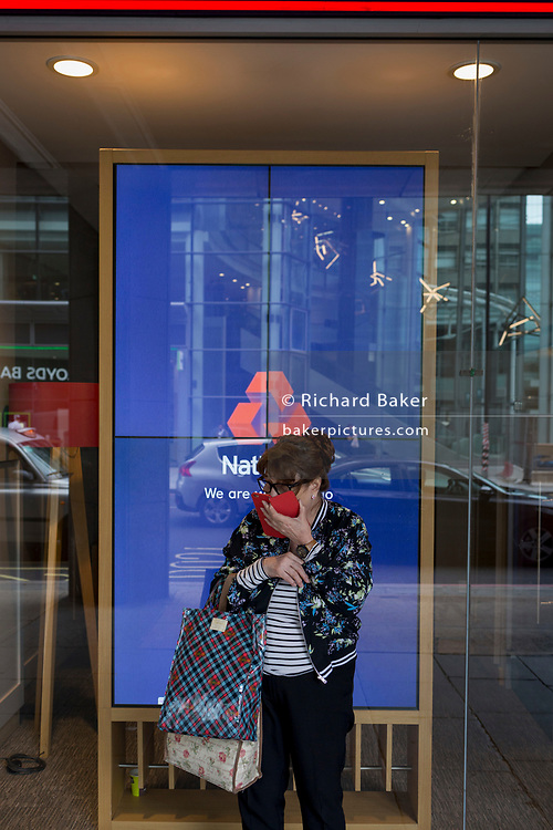 A woman uses her smartphone for a private conversation outside the branch of Natwest Bank on Victoria Street, on 6th September 2017, in London, England.