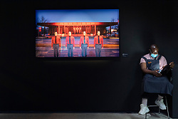 © Licensed to London News Pictures. 28/07/2020. London, UK. A Design Museum staff member sits next to a photograph in front of a Kraftwerk photograph by Peter Boettcher on display at The Design Museum exhibition 'Electronic: From Kraftwerk to The Chemical Brothers'. The exhibition explores the hypnotic world of electronic music and discovers its global impact from underground movements to the mainstream  and features appearances from the likes of Jeff Mills, Ellen Allien, Jean-Michel Jarre and more. It will also feature a 3-D experience surrounding electronic pioneers Kraftwerk, with the installation soundtracked by legendary DJ and producer, Laurent Garnier. Photo credit: Ray Tang/LNP