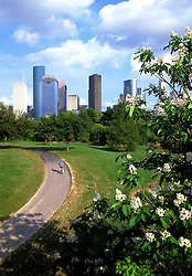 Man bicycling on a hike and bike path at Buffalo Bayou Park with view of downtown Houston, Texas skyline.