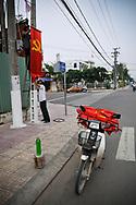 Vietnamese men hang communist flags in a street of Nha Trang, Vietnam, Southeast Asia