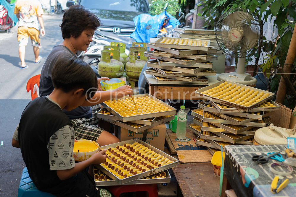 An Indonesian woman and her son making sweets in the street on 9th June 2018, Jakarta, Java, Indonesia.