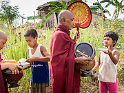 25 MAY 2013 - MAE SOT, TAK, THAILAND: Burmese children wait to give food to a group of Burmese monks and novices in an unofficial village of Burmese refugees north of Mae Sot, Thailand. They live on a narrow strip of land about 200 meters deep and 400 meters long that juts into Thailand. The land is technically Burma but it is on the Thai side of the Moei River, which marks most of the border in this part of Thailand. The refugees, a mix of Buddhists and Christians, settled on the land years ago to avoid strife in Myanmar (Burma). For all practical purposes they live in Thailand. They shop in Thai markets and see their produce to Thai buyers. About 200 people live in thatched huts spread throughout the community. They're close enough to Mae Sot that some can work in town and Burmese merchants from Mae Sot come out to their village to do business with them.   PHOTO BY JACK KURTZ