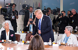 U.S. President Donald Trump, centre, takes his seat after arriving late for the G7 and Gender Equality Advisory Council Breakfast, as IMF Managing Director Christine Lagarde, left, and Canadian Lt.-Gen. Christine Whitecross look on at the G7 leaders summit in La Malbaie, Que., on Saturday, June 9, 2018. Photo by Justin Tang/CP/ABACAPRESS.COM