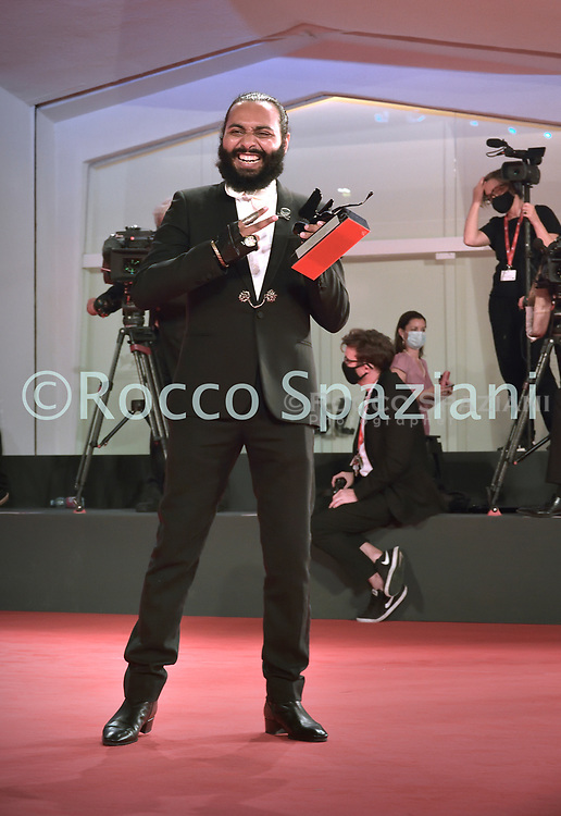 VENICE, ITALY - SEPTEMBER 12: Director Ismael El Iraki poses with the Orizzonti Award for Best Actress he received on behalf of Moroccan singer and actress Khansa Batma at the winners photocall at the 77th Venice Film Festival on September 12, 2020 in Venice, Italy.<br /> (Photo by Rocco Spaziani)