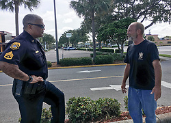 September 9, 2017 - Florida, U.S. - Tampa police Sgt. Ron Graham talks with John Tsikurios, who is homeless, about seeking shelter before the arrival of Hurricane Irma. Tsikurios declined an offer of a ride to one of several shelters in Tampa, saying he had enough money for a motel for the night, but wasn't sure about Sunday. (Credit Image: © Dan Sullivan/Tampa Bay Times via ZUMA Wire)