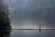 Two hikers walking over the floating bridge at Sasamat Lake in Port Moody, British Columbia, Canada.  White Pine Beach (popular during the summer months) is just around the corner from here and along with Sasamat Lake lies within Belcarra Regional Park.