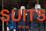Trendy blue suits with red lettering on display in a central London menswear shop. Three headless figures appear as if walking towards the viewer, only in the store window. The word Suits stretches across the width of the window but the lettering below that states how much the items for sale are, is below this bottom line. The shop is on London's Oxford Street, an east to west road long known for clothing and low-cost fashion - and before that, for the route that condemned criminals would take towards the gallows at nearby Tyburn.