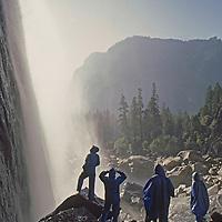 Hikers in mist below Lower Yosemite Falls in Yosemite Valley.