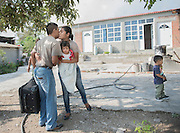 """Outside of their home, Sabina gives a farewell kiss to Rosalino, and it will be the last kiss shared for nine months. """"I'm not able to talk with my family often, so I miss them,"""" Rosalino said. """"But everything has a sacrifice. Everything you need has a price."""" Nick Wagner / Alexia Foundation"""