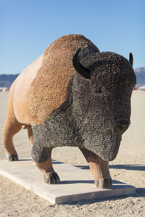 Tatanka<br /> by: Peter Hazel<br /> from: Reno, NV<br /> year: 2019<br /> <br /> Tatanka is an Indian word for buffalo. For the Northern Plains people Tatanka meant life. Ceremonies and daily life revolved around sacred reverences to Tatanka. They relied upon the bison for food, clothing, housing, tools, just to name a few. This piece is a 9′ tall mosaic buffalo created in Reno, NV by large scale sculpture artist Peter Hazel. The piece is made up of thousands of handmade tiles of various colors, textures, and sizes.<br /> <br /> https://burningman.org/event/brc/2019-art-installations/?yyyy=&artType=B#a2I0V000001T9wBUAS
