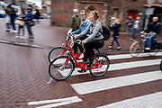 Een man en vrouw fietsen op een MacBike huurfiets over het Muntplein in Amsterdam.<br /> <br /> A man and woman cycle on a MacBike rental bike at the Munt Square in Amsterdam.