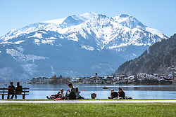 THEMENBILD - Menschen sitzen im Gras und auf einer Parkbank am Nordufer des Zeller Sees. Im Hintergrund Zell am See und die umliegende Bergwelt, aufgenommen am 20. April 2019, Zell am See, Österreich // People sit in the grass and on a park bench on the northern shore of Lake Zell. In the background Zell am See and the surrounding mountain world on 2019/04/20, Zell am See, Austria. EXPA Pictures © 2019, PhotoCredit: EXPA/ Stefanie Oberhauser