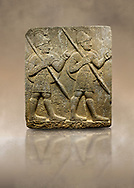 Hittite monumental relief sculpted orthostat stone panel from the Herald's Wall. Basalt, Karkamıs, (Kargamıs), Carchemish (Karkemish), 900-700 B.C. Military parade with soldiers. Anatolian Civilisations Museum, Ankara, Turkey<br /> <br /> Two helmeted soldiers marching soldiers in short skirts carry the shield on their backs and the spears in their hands. <br /> <br /> Against a brown art background. .<br />  <br /> If you prefer to buy from our ALAMY STOCK LIBRARY page at https://www.alamy.com/portfolio/paul-williams-funkystock/hittite-art-antiquities.html  - Type  Karkamıs in LOWER SEARCH WITHIN GALLERY box. Refine search by adding background colour, place, museum etc.<br /> <br /> Visit our HITTITE PHOTO COLLECTIONS for more photos to download or buy as wall art prints https://funkystock.photoshelter.com/gallery-collection/The-Hittites-Art-Artefacts-Antiquities-Historic-Sites-Pictures-Images-of/C0000NUBSMhSc3Oo