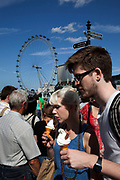 Tourists eating ice cream cross Westminster bridge by the River Thames at Westminter, London. With the iconic London Eye behind this is one of the busiest areas for tourism in the city.