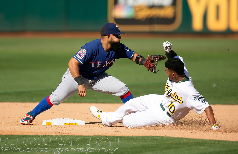 Oakland Athletics' Marcus Semien (10) slides safely into second base with an RBI double as Texas Rangers second baseman Rougned Odor (12) takes the late relay during the ninth inning of a baseball game, Sunday, Sept. 22, 2019, in Oakland, Calif. The Rangers defeated the Athletics 8-3. (AP Photo/D. Ross Cameron)