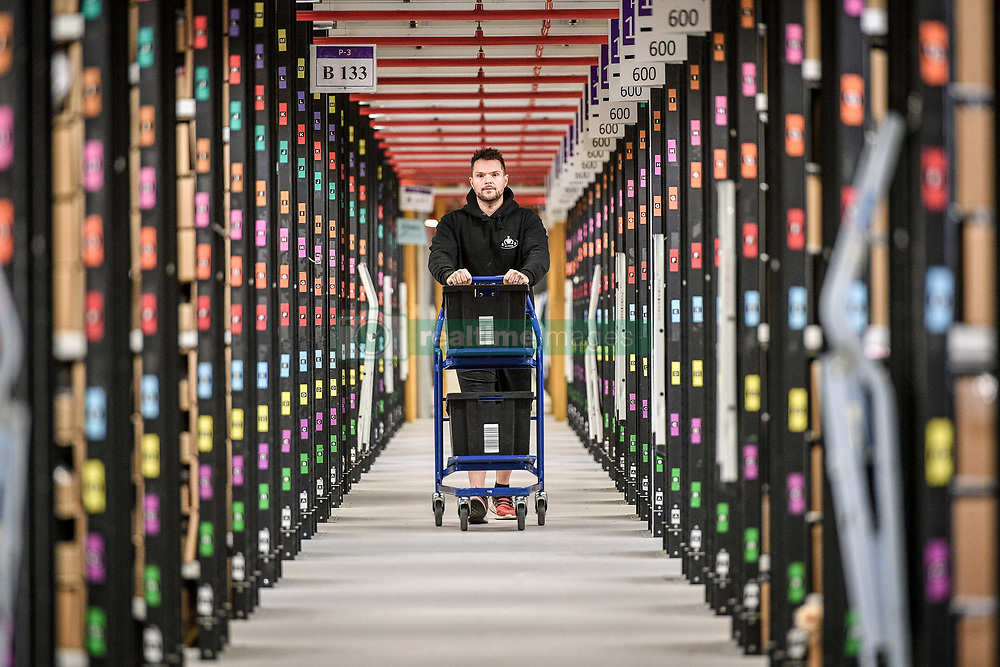 A worker walks between thousands of racks at Amazon's fulfillment centre in Swansea, in the run up to Black Friday.