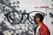Pedestrians walk past a store selling Japanese eye wear in Shanghai, China, on Friday, Oct. 2, 2015.