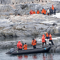 Guests board an inflatable boat (zodiac) after visiting a penguin colony at Port Lockroy, Antarctica.