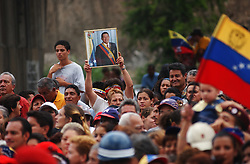 A crowd gathers to listen to President Hugo Chavez as he speaks at the inauguration of a government subsidized market called Mercal.