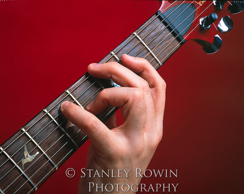 Neck and head of a guitar showing fingerboard frets and strings, close-up detail, with hand