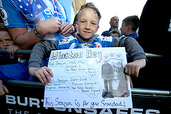 A Huddersfield Town fan holds up a sign outside the stadium before the match begins