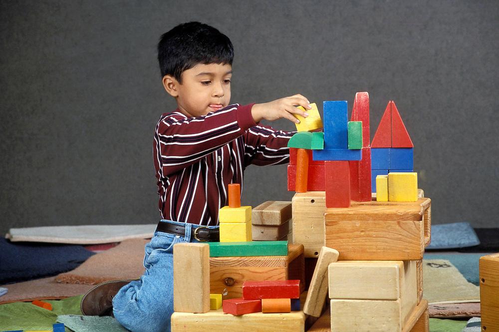 Austin, Texas:  Five year old Hispanic boy plays with blocks in kindergarten classroom.<br /> ©Bob Daemmrich /