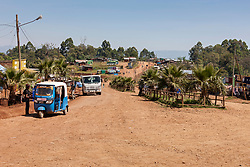 Jinrikisha on dirt road with other vehicles and trees against sky