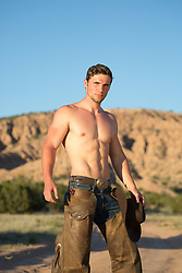 muscular shirtless cowboy in chaps outdoors