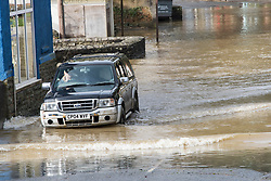 © Licensed to London News Pictures. 10/03/2020. Builth Wells, Powys, Wales, UK. A motorist in a 4WD vehicle drives through flood water on the A483 road through Builth Wells in Powys, Wales, UK. after the river Wye levels rose dramatically overnight following heavy rainfall in Mid Wales yesterday and last night. According to Natural Resources Wales website, the level reached a peak of 4.21 metres. The website also shows that an all time high level of 5.05 metres was reached at the Builth Wells gauge on 16th February 2020. Photo credit: Graham M. Lawrence/LNP