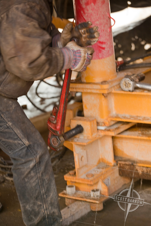 A worker adjusting and assembling metal supports in a factory or construction situation.