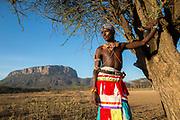A Samburu warrior in Kenya with Mount Ololokwe in the background.