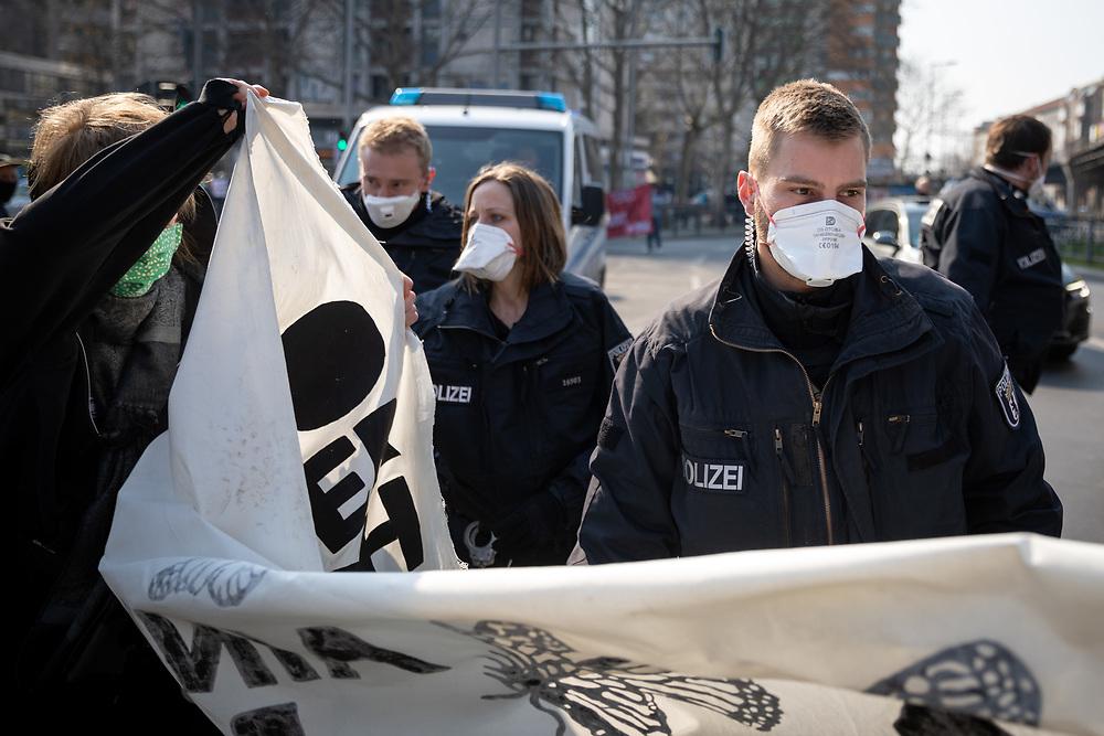 An die 200 Demonstranten mit Atemschutzmasken protestieren während der Verordnung mit Ausgansbeschränkungen und Kontaktverbot zur Eindämmung der COVID-19 - Pandemie (Coronavirus SARS-CoV-2)  unangemeldet und mit Sicherheitsabstand am Kottbusser Tor in Berlin Kreuzberg gegen Zwangsräumungen, soziale Missstände und für eine Aufnahe von Geflüchteten. Polizisten mit Atemschutzmasken drängen die Demonstranten auf den Bürgersteig.<br /> <br /> [© Christian Mang - Veroeffentlichung nur gg. Honorar (zzgl. MwSt.), Urhebervermerk und Beleg. Nur für redaktionelle Nutzung - Publication only with licence fee payment, copyright notice and voucher copy. For editorial use only - No model release. No property release. Kontakt: mail@christianmang.com.]