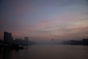 Thick fog in evening light over London making a peaceful yet eerie landscape atmosphere as structures appear and disappear over the River Thames. Modern and old industrial and commercial architecture is releaved through a mist which lasted tthrough the entire day.