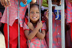 Children wait for the arrival of Prince Harry in Soufriere on the island of St Lucia during the second leg of his Caribbean tour.