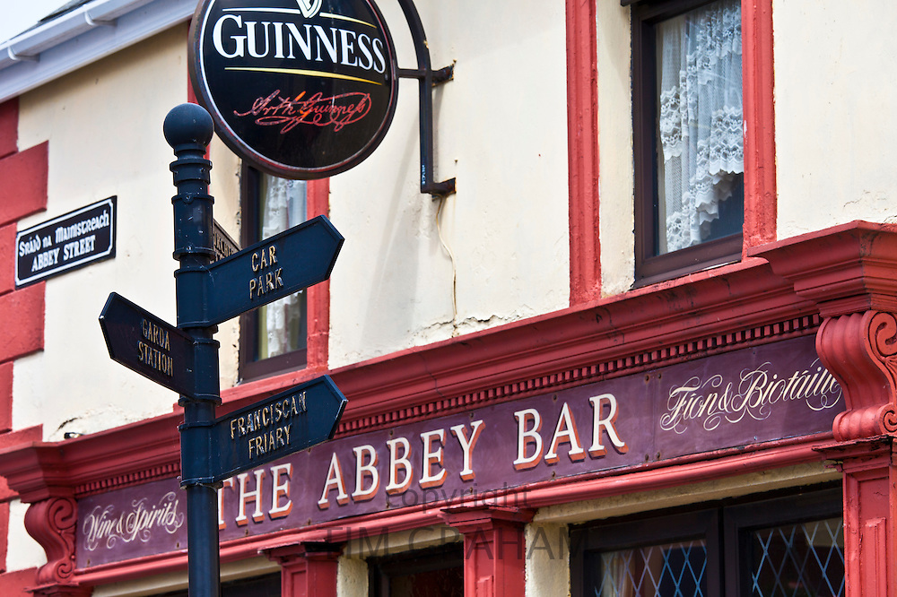 Signpost to Garda and Car park next to Guinness advertisement at The Abbey Bar in Abbey Street, Timoleague, West Cork, Ireland
