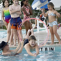 Riley Wilson, 8, dives through hoops as his instructor, Steve Singleton, 18, holds them during swimming lessons at Independence Park Swimming pool in Pearland, 06/03/03.  Watching in the background Marissa Merritt, 8, left, Nathan Carter, 7, Jessica Murry, 10, and Shelby Estes, 5.