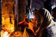 """19th March 2015, New Delhi, India. A woman prays to Djinns in the hopes of getting her wishes granted in the ruins of Feroz Shah Kotla in New Delhi, India on the 19th March 2015<br /> <br /> PHOTOGRAPH BY AND COPYRIGHT OF SIMON DE TREY-WHITE a photographer in delhi<br /> + 91 98103 99809. Email: simon@simondetreywhite.com<br /> <br /> People have been coming to Firoz Shah Kotla to leave written notes and offerings for Djinns in the hopes of getting wishes granted since the late 1970's. Jinn, jann or djinn are supernatural creatures in Islamic mythology as well as pre-Islamic Arabian mythology. They are mentioned frequently in the Quran  and other Islamic texts and inhabit an unseen world called Djinnestan. In Islamic theology jinn are said to be creatures with free will, made from smokeless fire by Allah as humans were made of clay, among other things. According to the Quran, jinn have free will, and Iblīs abused this freedom in front of Allah by refusing to bow to Adam when Allah ordered angels and jinn to do so. For disobeying Allah, Iblīs was expelled from Paradise and called """"Shayṭān"""" (Satan).They are usually invisible to humans, but humans do appear clearly to jinn, as they can possess them. Like humans, jinn will also be judged on the Day of Judgment and will be sent to Paradise or Hell according to their deeds. Feroz Shah Tughlaq (r. 1351–88), the Sultan of Delhi, established the fortified city of Ferozabad in 1354, as the new capital of the Delhi Sultanate, and included in it the site of the present Feroz Shah Kotla. Kotla literally means fortress or citadel."""