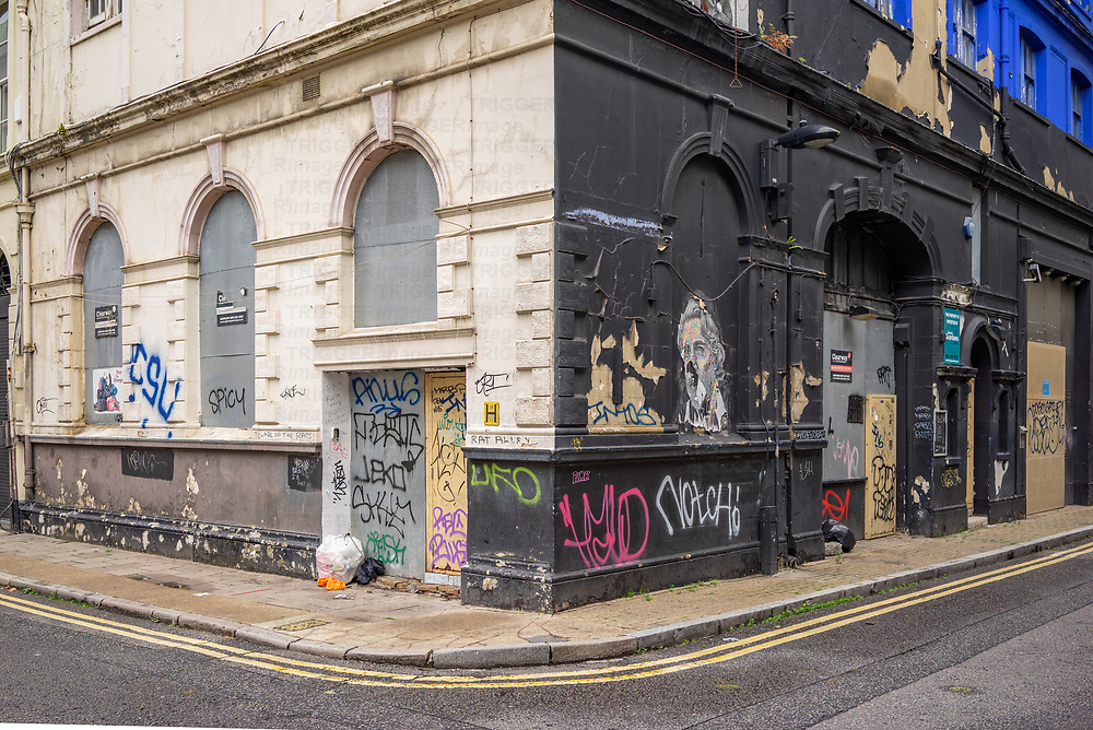 West Central Street in Bloomsbury, London with an abandoned building with peeling paint and graffiti on the walls
