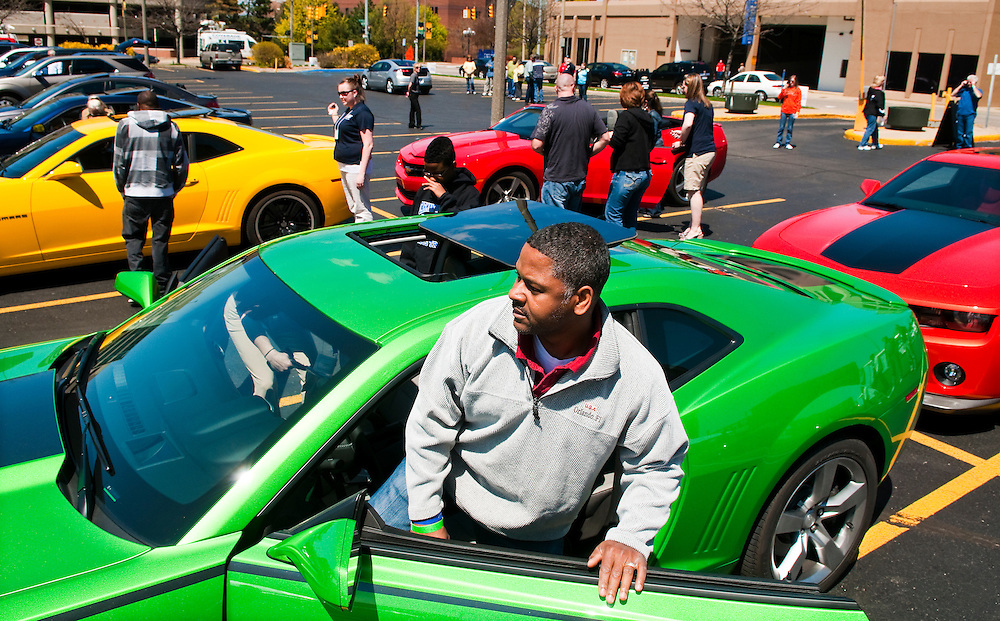 Matt Dixon | The Flint Journal..Larry Dunn, 48, of Flint gets into a 2011 Chevrolet Camaro SS while attendees wait to test drive other Camaros (back) during General Motors' Ride and Drive event in downtown Flint Saturday. Over 30 GM vehicles, were available to test drive at the event which was open to the general public.