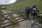 Walkers open a farmers gate and enter a field while keeping to a public footpath on 13th April 2017, in Settle, Yorkshire, England.