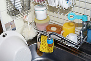 kitchen sink with various soaps and sponges