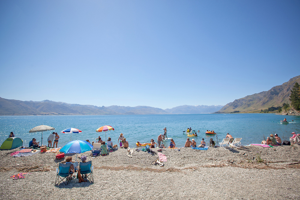 Holiday makers relax around the edge of Lake Hawea on a hot blue sunny summers day.