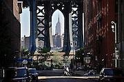 A delivery man bikes early in the morning on Washington Street in DUMBO, Brooklyn, with the Manhattan Bridge and the Empire State Building in the background.