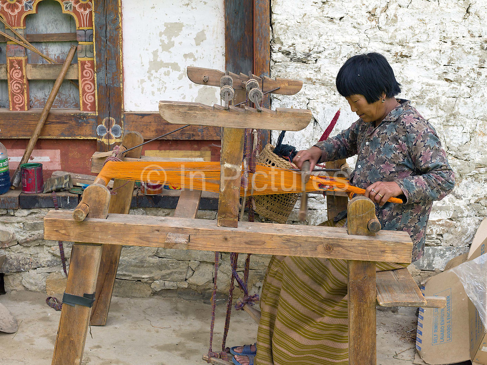 Dhenchen Chezom weaves a woollen yathra skarf on a Tibetan style loom outside her farmhouse in the Tang Valley, Bumthang, Central Bhutan. Yathra is a hand woven fabric made from the wool of sheep and yak and is the most famous textile product of Bumthang. Yathra cloth is made into skarfs, jackets, blankets; table cloths and bags.