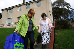 A women with Learning Disabilities leaves the supported flat where she lives; to go shopping with her support worker; Skipton; North Yorkshire, UK