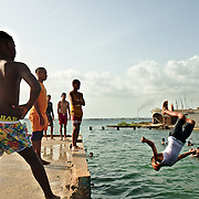 Boys using an abandoned pier close to Cienfuegos marina to dive on a hot Sunday.