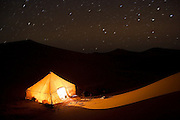 Star trails over a tent illuminated at night among sand dunes on a guided camel trek to the Erg Zehar region near M'hamid, Morocco.