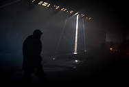 Inside one of the abandoned warehouses used by migrants as shelter in the old train depot. Light enters from some holes on the roof penetrating the thick smoke. Belgrade, Serbia. 15th January 2017. Federico Scoppa